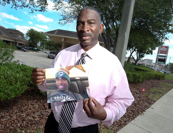 Ron Davis holds the last-known picture of his 17-year-old son Jordan Davis, who was shot and killed at this Jacksonville gas station Nov. 23, 2012. (Photo by Walter Coker.)